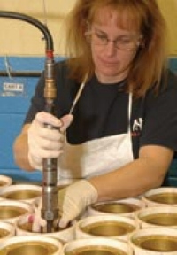 Using specialty tools Karen Dixon inserts a Heli-Coil in a Challenger rescue tool cylinder.
