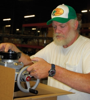 Gary Aplex, who is on Kochek's packing and shipping team, boxes a ball intake valve with a Storz head for shipment. Kochek ships to more than 30 countries.