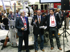 (1) In front of the platform of Spartan ERV's Telstar aerial with articulating boom, John Sztykiel (center), president and CEO of Spartan Motors, Inc. introduces Stefano Chmielewski (left), vice president of Volvo government sales, parent company of Renault, and Philippe Mis (right), Chairman of Gimaex Worldwide.