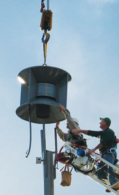 (5) When the rebuilt SD-10 siren was installed on its rooftop pedestal, a crane supported the siren while technicians used an aerial ladder to access the mounting bolts and electrical connections.