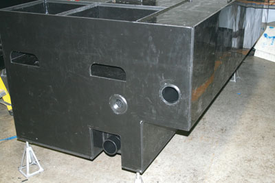 (5) This rectangular tank shows one type of water diffuser, an internal one-piece machined basket style, in the center tank fill connection. There is a sleeve above the notch on the right side. The two center side-by-side openings are for later attachment of foam cell fittings whose tanks are visible in the upper bulkhead.