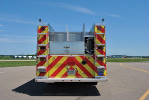 (9) Both sides at the rear of this CustomFIRE pumper for the St. Paul (MN) Fire Department have full height handrails on each side of custom width access steps to facilitate climbing while meeting the three-points-of- contact concept. Just visible on the compartment tops are the ends of two additional grab rails.