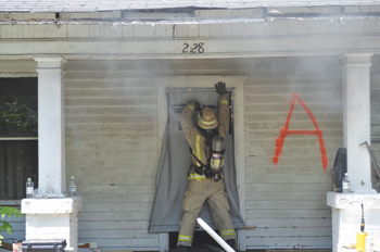 (1) Here, a firefighter deploys a portable door to control air track movement.