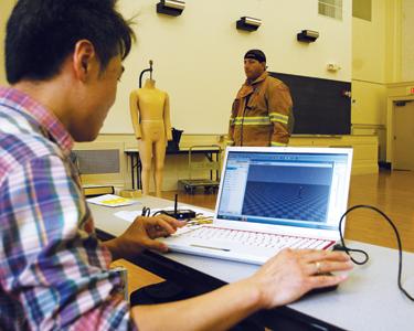 Huiju Park, Cornell University professor of fiber science and apparel design, records motion data of a firefighter wearing gear.