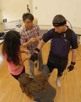Park and his students attach motion sensor gear to a firefighter in preparation for tracking data as the firefighter walks.