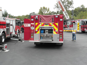This stainless steel pumper shows a functional rear step hydraulic rescue tool compartment and a swing-down ladder rack