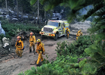 California Emergency Management Agency strike team firefighters are shown fighting a wildfire using a Rosenbauer-supplied Type III wildland apparatus.