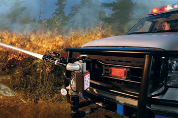 A Task Force Tips Tornado monitor mounted in the front-center of a brush truck demonstrates an attack against a wildland fire