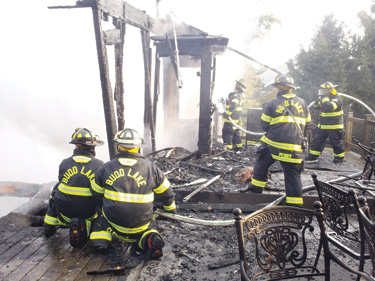 Budd Lake (NJ) Fire Department firefighters mop up at a structure fire
