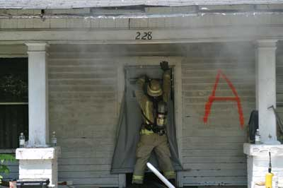 firefighter deploys an air curtain at a live burn at an acquired structure