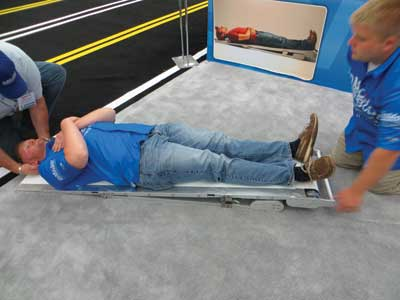 6 Once the head and neck are on the SpineBoard, the EMT releases the button and the conveyor belts stop. The EMT Standard model has a six-foot-long board