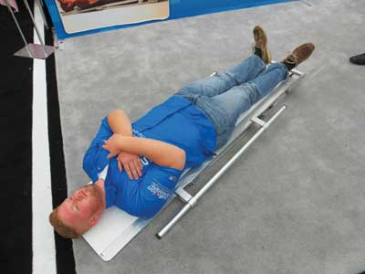 7 Once the head and neck are on the SpineBoard, the EMT releases the button and the conveyor belts stop. The EMT Standard model has a six-foot-long board