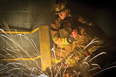 Firefighters operating wearing turnout gear.