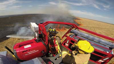 1 One tactic for fighting fine-fuels fires involves a firefighter riding on the apparatus exterior aiming a water stream directly at the base of the fire. Apparatus used for this tactic typically include a platform behind the cab where a firefighter can stand. (Photo courtesy of Blanchat Mfg. Inc