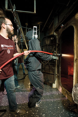 3 Virginia Tech engineering student Viktor Orekov backs up SAFFiR during its demonstration of its shipboard firefighting abilities aboard the USS Shadwell, a U.S. Navy experimental facility with a fire control laboratory.