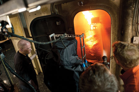 4 John Farley, a Virginia Tech engineering student, right, and two unidentified researchers watch as the Navy's robot operates a one-inch handline to extinguish a fire in a shipboard compartment.