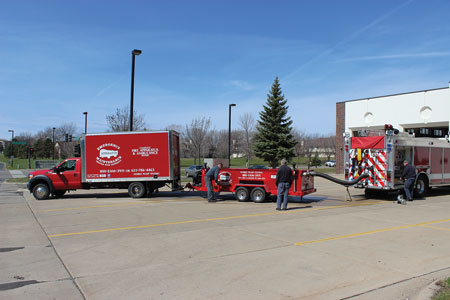 4 Emergency Apparatus Maintenance staff set up their equipment to pump test a Maple Grove (MN) Fire Department pumper. (Photo courtesy of Emergency Apparatus Maintenance