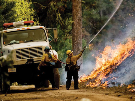 16 A Type 3 engine crew uses traditional red rubber booster line during a wildland fire. (Photo courtesy of the U.S. Forest Service