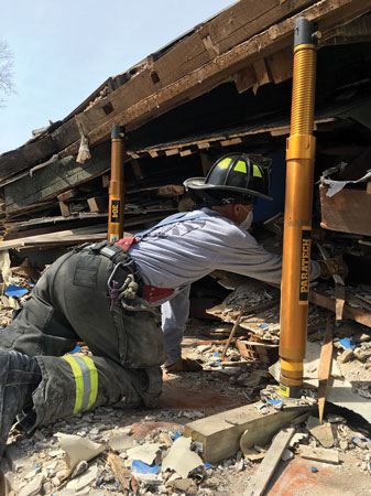 12 A firefighter searches for mannequins in an intentionally collapsed house. He is being protected from further collapse by the gray Paratech Acme Thread Strut. (Photo courtesy of Paratech Inc