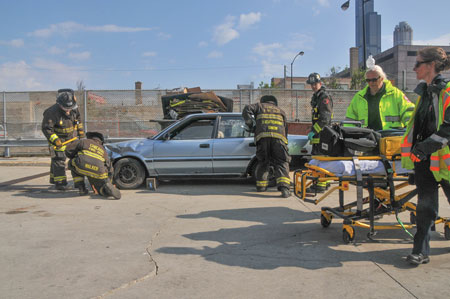 2 Chicago firefighters prepare to tear into a car with Hurst Generation 2 eDRAULIC spreaders and cutters as part of the department's 2016 EMS Day demonstration.