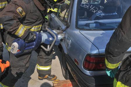 3 A Chicago firefighter uses a Hurst eDRAULIC SP310E2 spreader to open a car door.