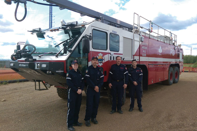 1 Members of Suncor's emergency services stand next to the company's Striker 8x8 that responded to the Fort McMurray fire in Alberta, Canada. (Photo courtesy of Suncor.)