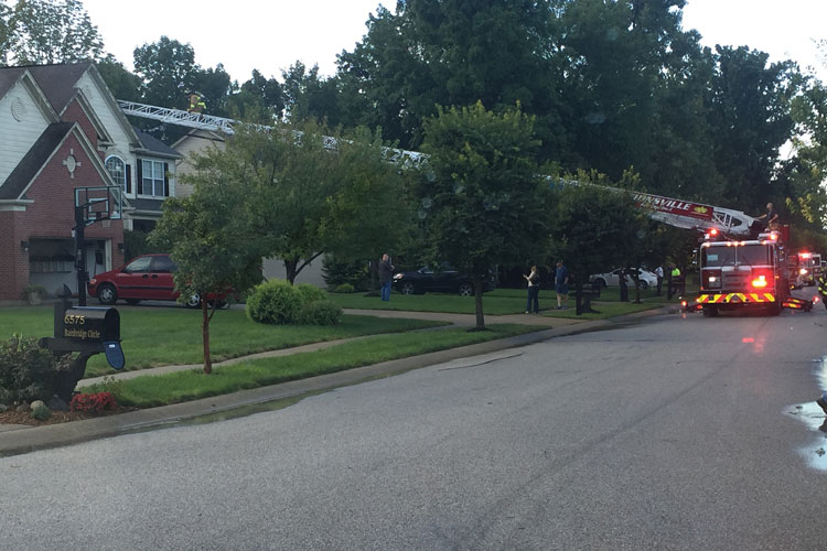6 Zionsville's CR137 ladder easily reaches the roof of a large house set well back from the street during this evening fire call for a house hit by lightning. [Photo courtesy of the Zionsville (IN) Fire Department.]