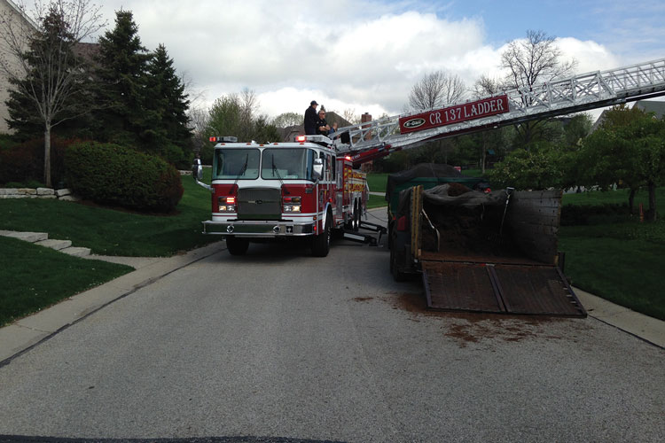7 The CR137 aerial ladder demonstrates it can handily go over roadside obstructions to reach a house set back from the street. [Photo courtesy of the Zionsville (IN) Fire Department.]