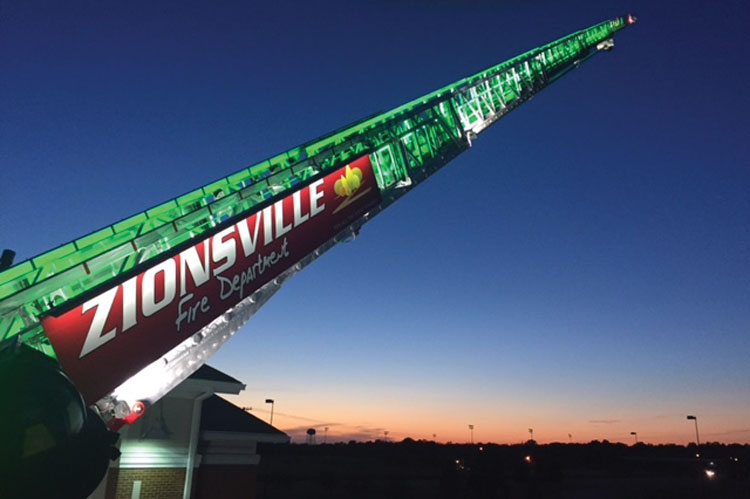 8 Zionsville wanted to give recognition of its firefighters to the community, so it has large lighted name signs placed on each side of the aerial and lit the ladder with green LED night lighting. [Photo courtesy of the Zionsville (IN) Fire Department.]