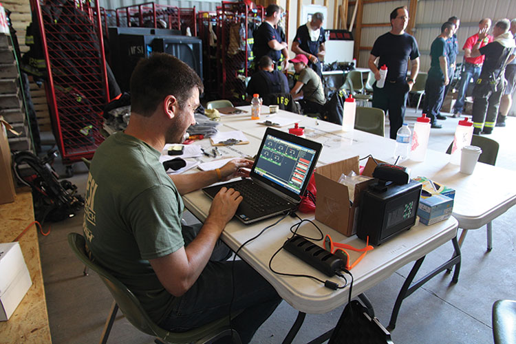 4 An Illinois Fire Service Institute (IFSI) researcher readies a WASP monitoring laptop while firefighters get set to don structural firefighting gear and take part in live fire testing. (Photo courtesy of Illinois Fire Service Institute.)