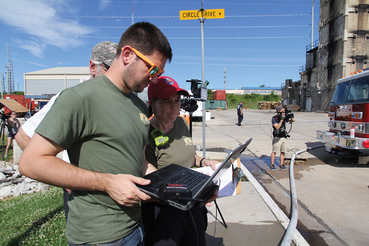 5 IFSI researchers study the readouts on their laptop during live fire testing of the WASP system at the IFSI's training center. (Photo courtesy of Illinois Fire Service Institute