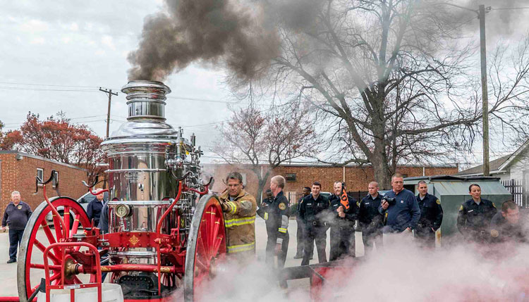 Firefighters operate an antique steam boiler engine