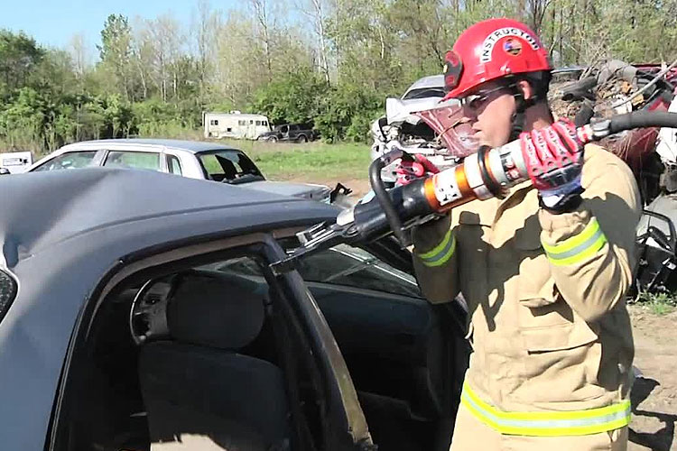 A firefighter uses a combi-tool to attack posts in a vehicle during extrication operations