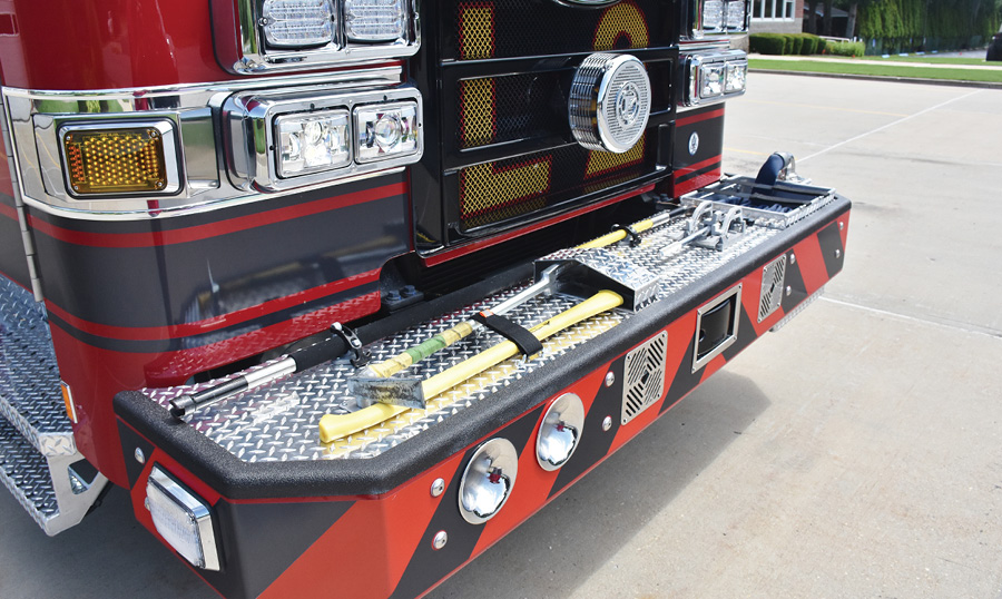 The front bumper of the truck carries forcible entry tools, a hook, and a 1¾-inch handline.