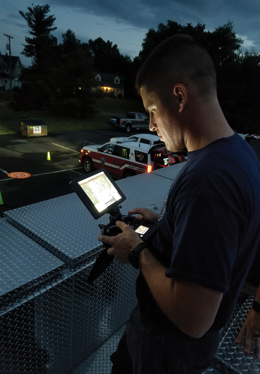 A Millstone Valley firefighter controls one of the department's drones during a night operation.