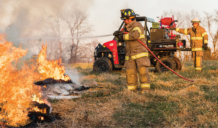 A firefighter uses a booster line off an 1800 Series reel made by Hannay and mounted on a Polaris utility terrain vehicle. (Photos 5-7 courtesy of Hannay Reels.)