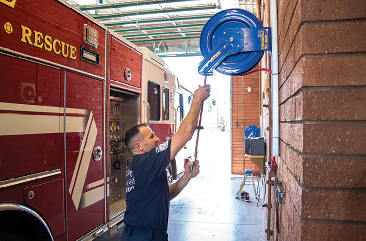 A Tempe (AZ) firefighter prepares to inflate apparatus tires with a utility air line coiled on a P Series reel made by Cox Reels.