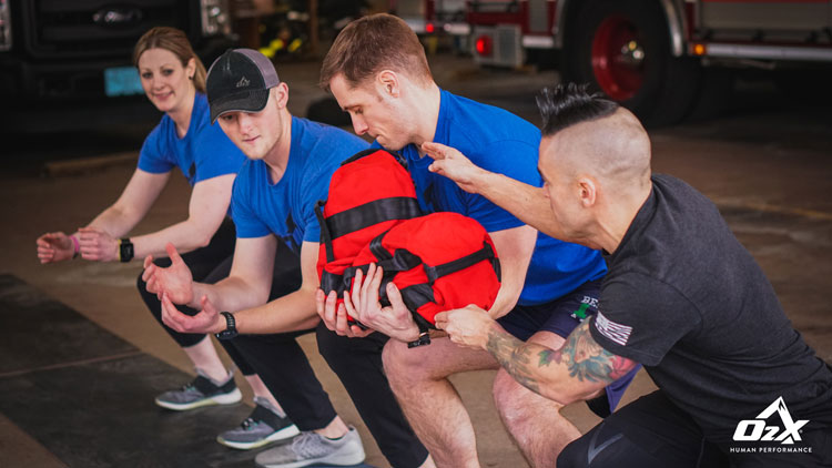 O2X trainer working with firefighters in a drill