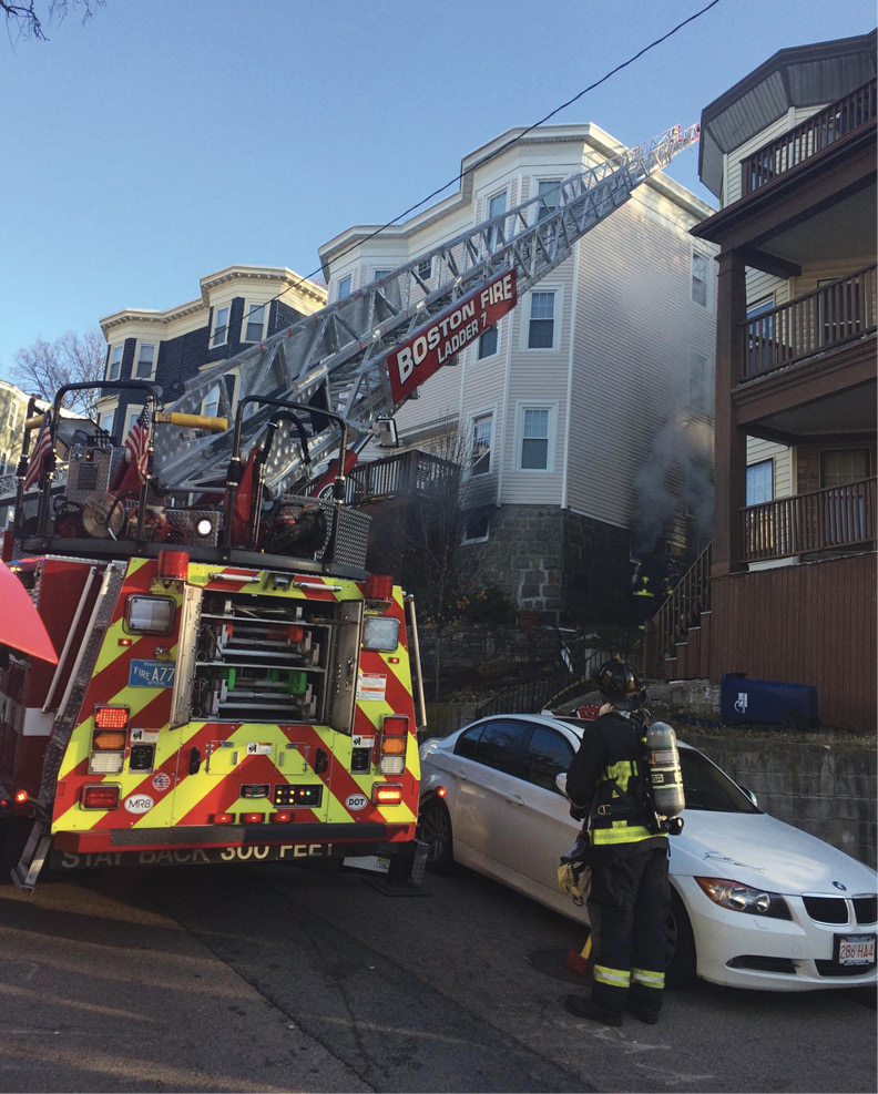 The ladder truck's jacks are fully deployed on a tight street.