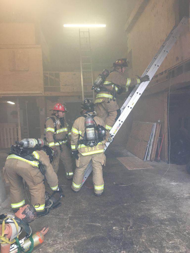 Firefighters climb to the training area for a live burn.