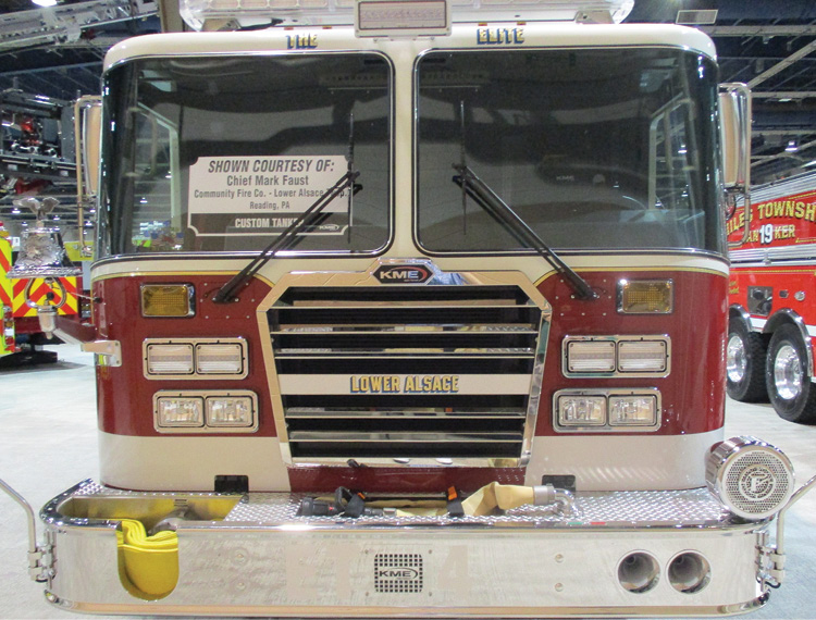 A KME rig with the quad-light configuration on each side of the grille. A single directional light is on top. Dual warning lights are in a separate bezel mounted above dual headlights in another bezel. The lower two bezels are offset following the contour of the grille.
