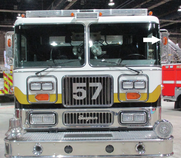 An older model Seagrave with similar light module panels with dual warning lights on top, a single guide-arrow-type directional in the middle, and dual headlights on the bottom. The arrow shows an auxiliary amber light on the West Coast mirror. Regardless if used as a marker or a directional light, it is far enough away from warning and headlights to not be obscured. Another advantage is indicating the width of the vehicle to oncoming traffic. All rigs should be equipped with them.