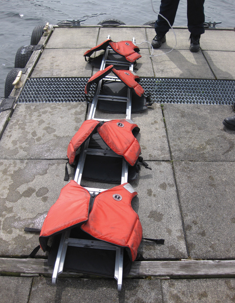 Buckling at least four life jackets to the ladder will keep it afloat.