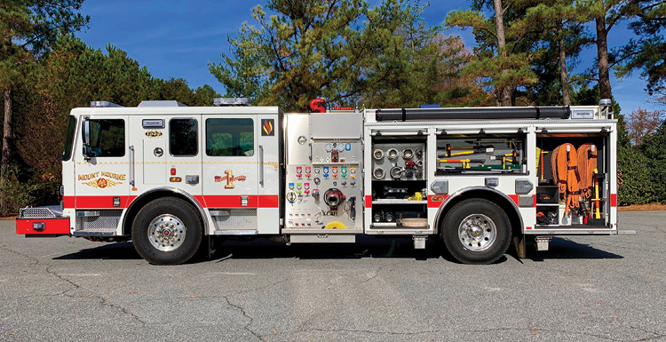 The driver's side of the pumper. It has a simple pump panel layout, a booster line, and a deck gun on top. It carries normal engine company fittings, forcible entry tools, flex hose on top, and 1¾-inch hose packs.