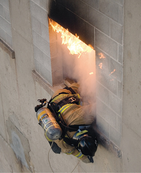 A firefighter bails out of a window using the Petzl EXO personal escape system.