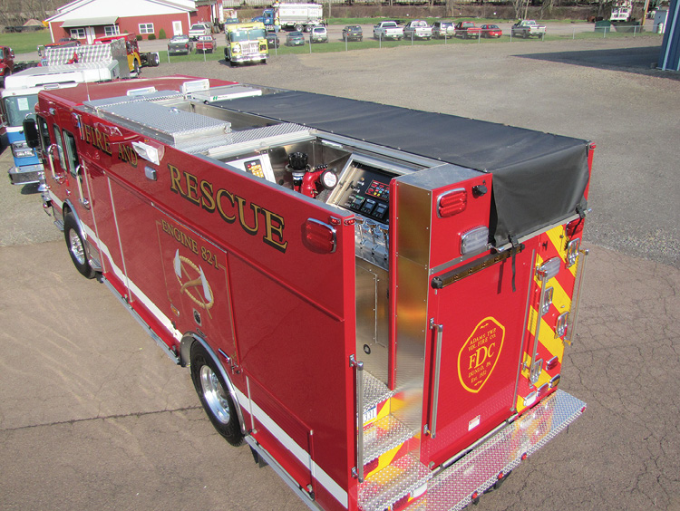 4 Guys built this rear-mount pumper on a Spartan chassis for the Adams Township (PA) Fire Department with a pump panel at the top left rear of the vehicle, accessed by a three step stairway.