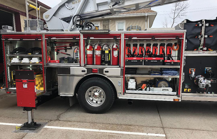 The truck's officer-side compartments hold extinguishers, portable lighting, hand lamps, forcible entry tools, and saws.