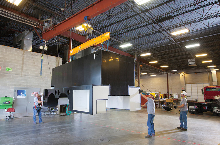 Workers are using an overhead crane to move an All-Poly body. More than 99 percent of Midwest's production is with high-impact-resistant copolymer polypropylene.