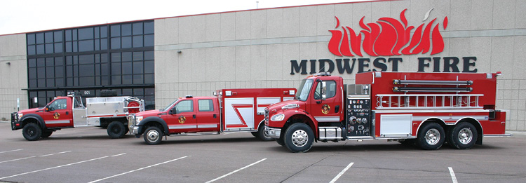 This line-up in front of Midwest's factory shows another variation of a brush truck with a treadplate body, a small rescue truck, and a large-capacity tanker-pumper on a two-door commercial chassis with a tandem rear axle.