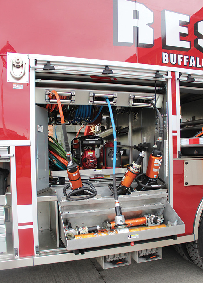The hydraulic rescue tool compartment on the Buffalo rescue truck has a slide-out, angled-down tray for the tools and three hose reels at the top.